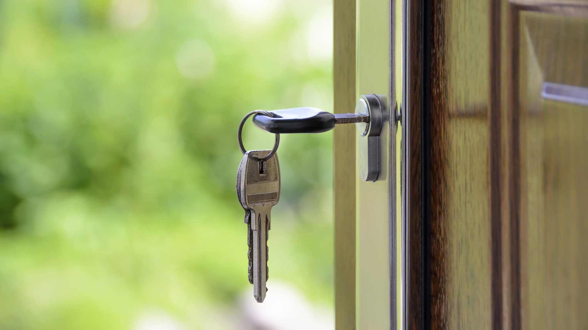 A key on an open door denoting real estate