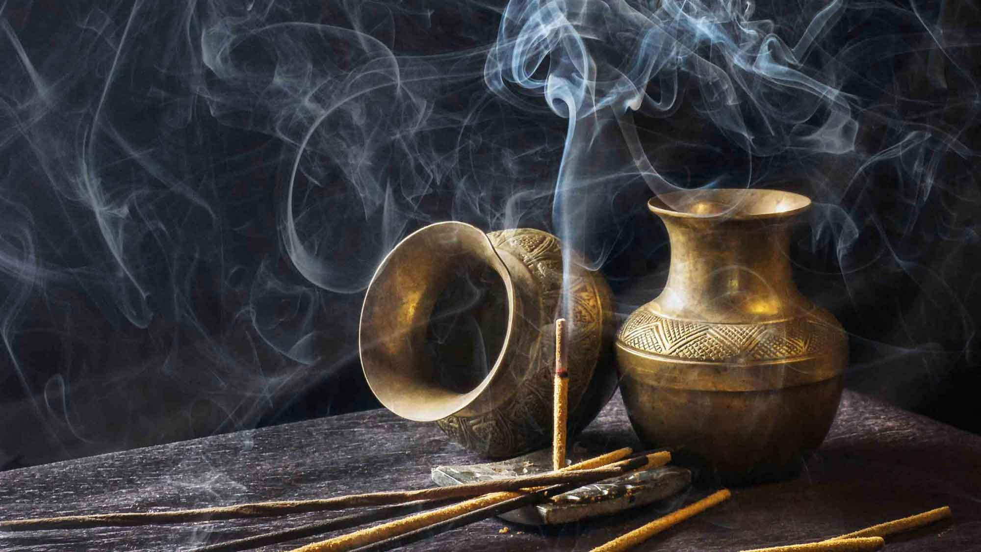 Two small golden jugs and a burning incense on a wooden table