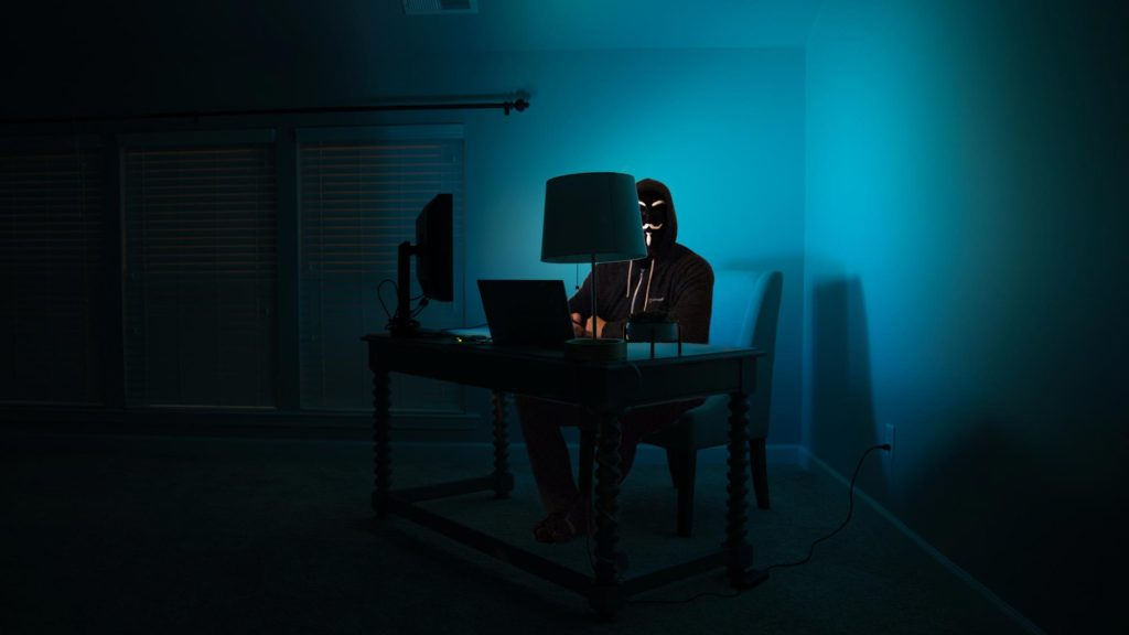 man at a computer disguised as an anonymous hacker in the dark