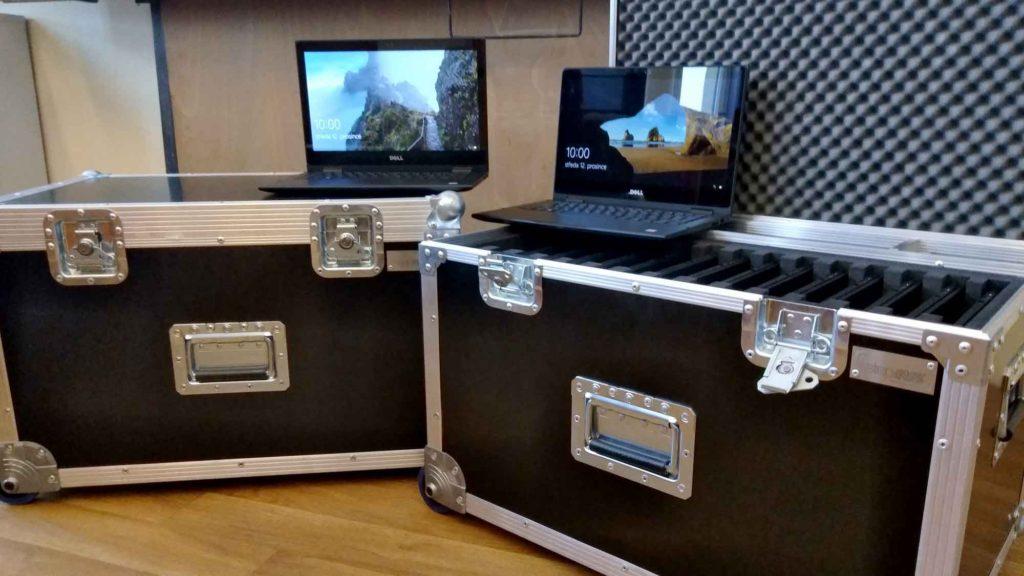 Pohled na dva notebooky umístěné na kufry