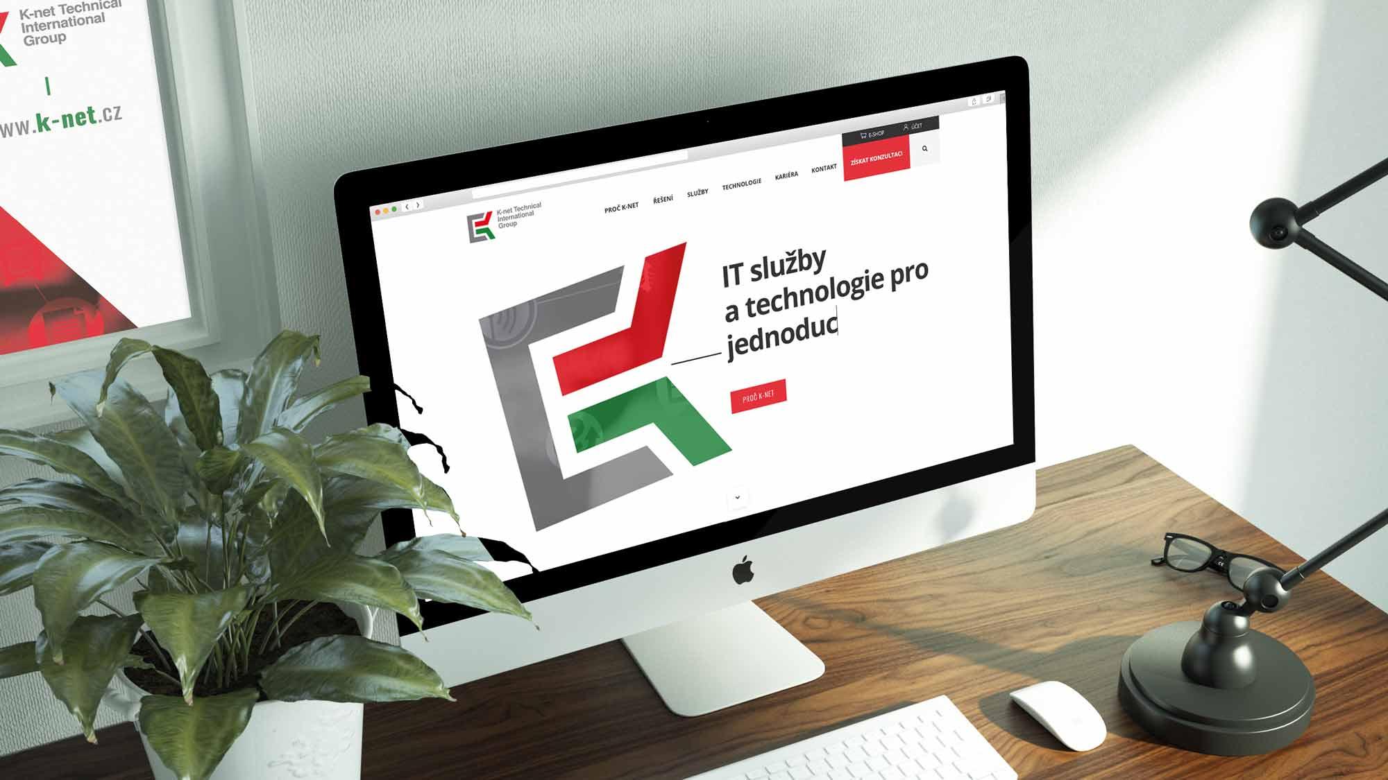 Pohled na iMac, který zobrazuje domovskou stránku K-net, na stole vedle zelené rostliny