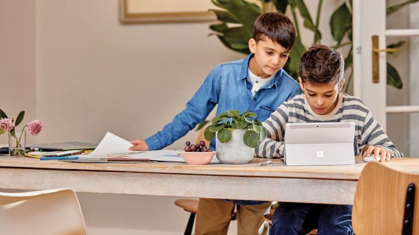 Obrázek 2 dětí studujících na dálku s využitím počítače Microsoft Surface