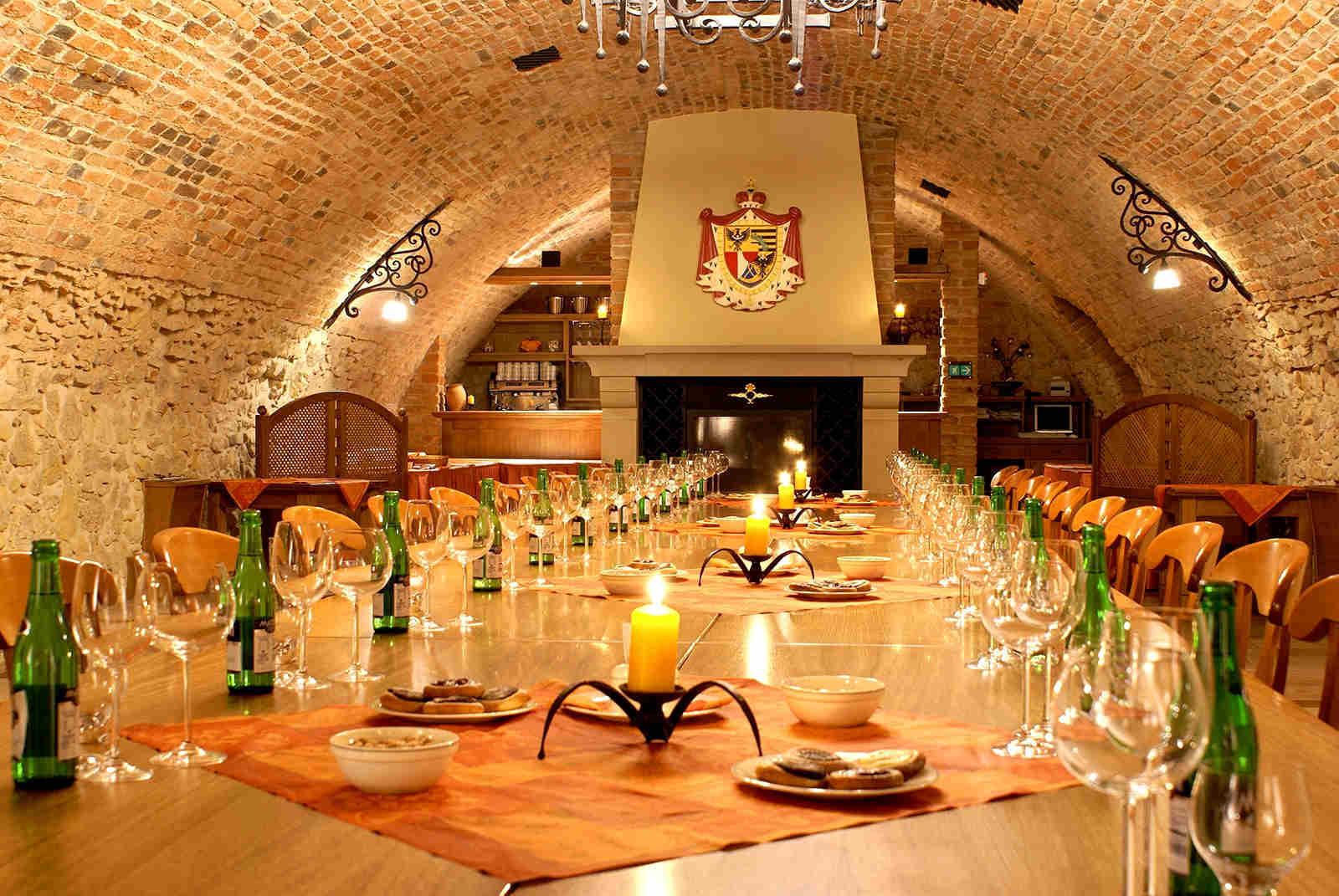 Pohled na upravený stůl se sklenicemi ve vinařském sklípku