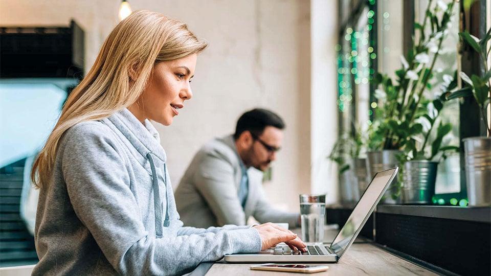 Žena píše do notebooku, vpozadí sedí muž.