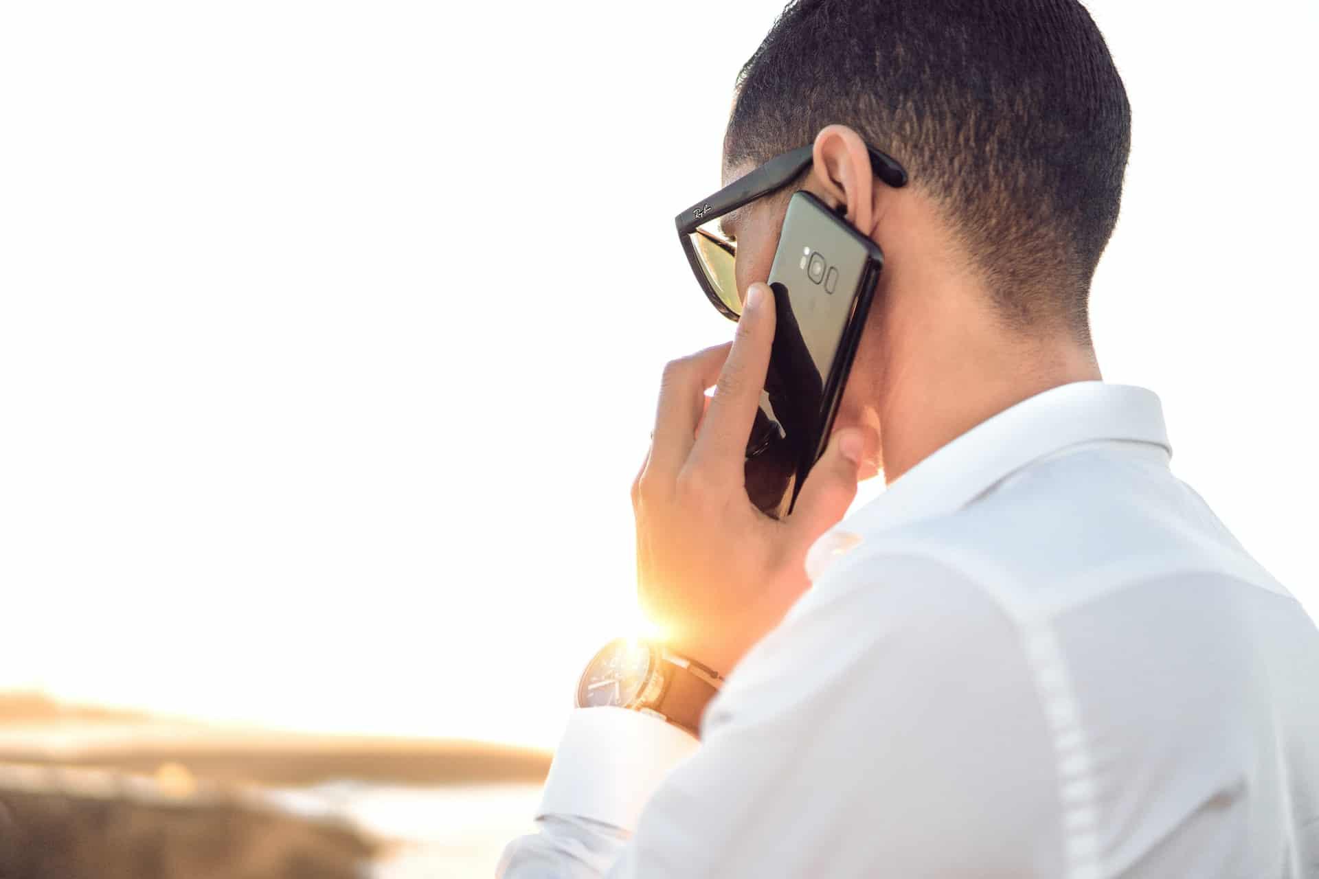 Mladý muž telefonuje na slunci
